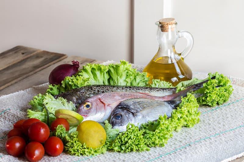 新鲜看见低音和海鲷与有些成份在蔬菜沙拉在木背景 库存照片