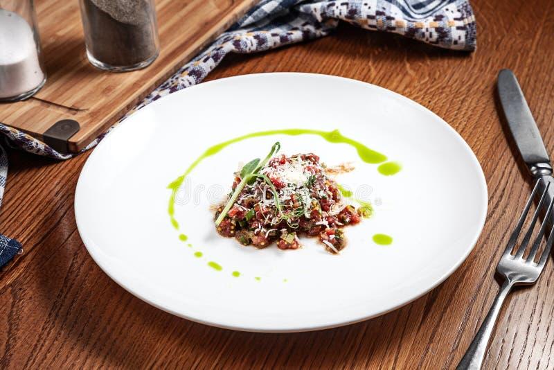 新鲜自创鲜美碎牛肉洋葱鸡蛋混合菜在白色板材 未加工的牛肉 供食的小牛肉鞑靼与设计的拷贝空间 食物的关闭 库存图片