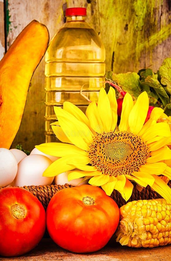 新鲜蔬菜、花、鸡蛋和一个瓶油 免版税库存照片