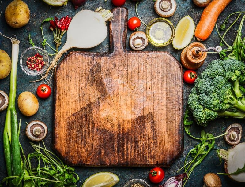 新鲜蔬菜和成份烹调的在葡萄酒切板附近在土气背景,顶视图,地方文本的 免版税图库摄影