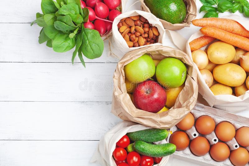 新鲜蔬菜和果子在自然eco友好的棉花和纸袋顶视图 零的浪费的食物购物和塑料自由 免版税库存图片