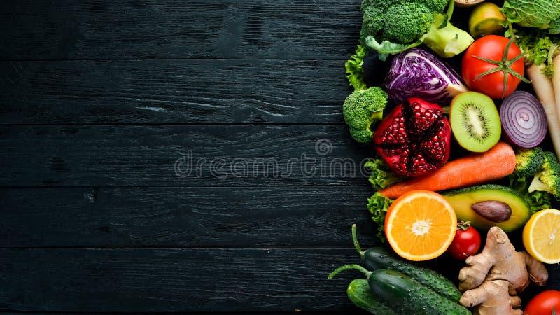 新鲜蔬菜和果子 在黑木背景的有机食品 免版税图库摄影