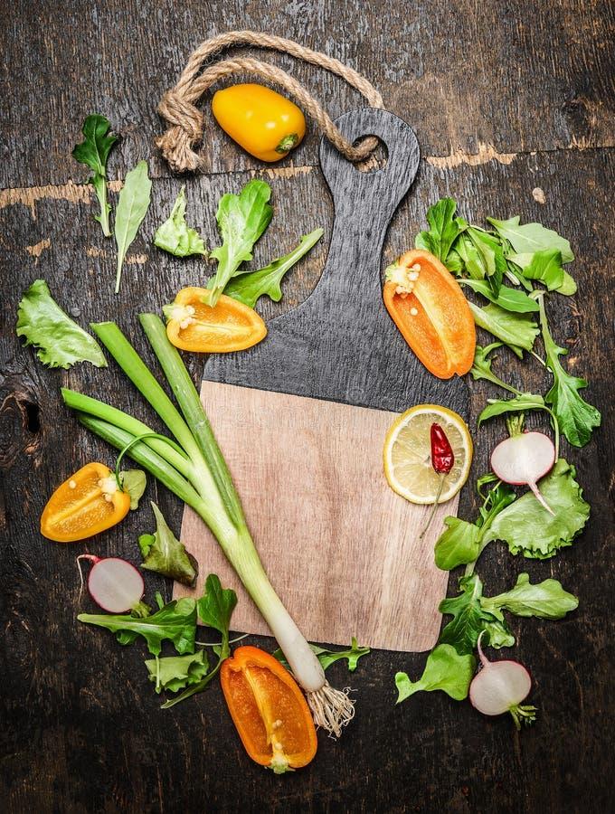 新鲜蔬菜和草本成份鲜美烹调的在空白的切板附近在土气木背景 免版税图库摄影