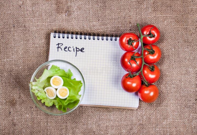新鲜蔬菜和食谱书在麻袋布 库存照片