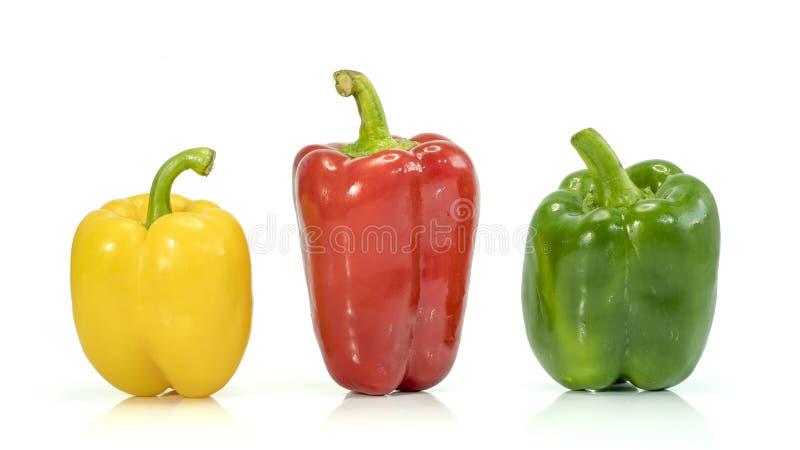 新鲜蔬菜在白色隔绝的三个甜红色,黄色,青椒 图库摄影