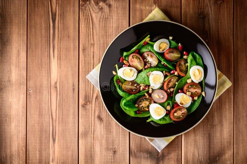 新鲜蔬菜沙拉用菠菜、西红柿、鹌鹑蛋、石榴种子和核桃在黑色的盘子在木桌上 库存照片
