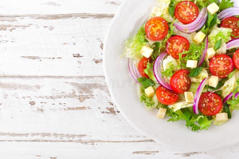 新鲜蔬菜沙拉用蕃茄、莴苣、葱和乳酪在白色木背景 食物健康素食主义者 免版税库存图片