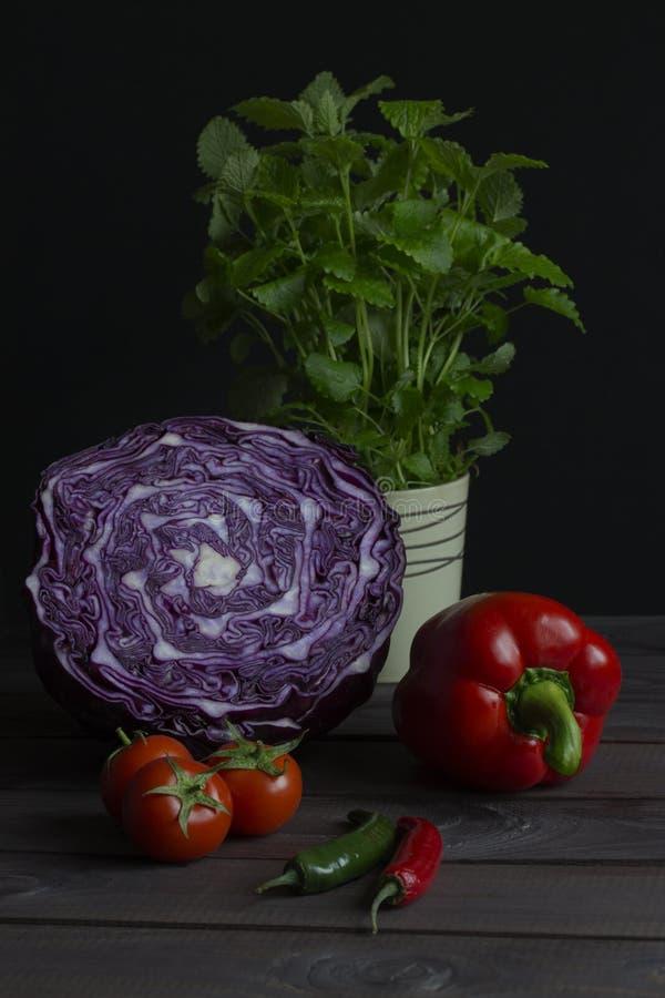 新鲜蔬菜红叶卷心菜辣椒粉蕃茄辣椒低调薄荷的静物画 被切的红叶卷心菜,绿色炽热辣椒 图库摄影