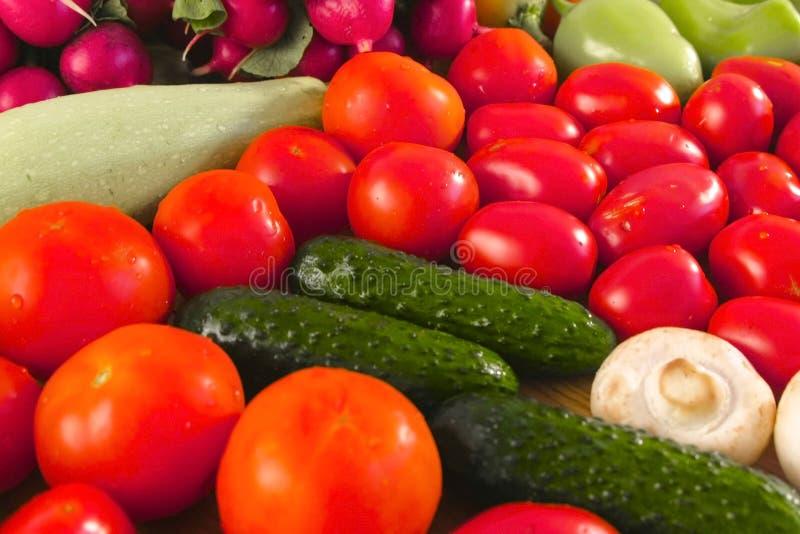 新鲜蔬菜蕃茄、黄瓜、夏南瓜、胡椒、绿色、萝卜和蘑菇在厨房用桌上 免版税图库摄影
