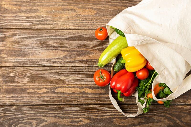 新鲜蔬菜蕃茄夏南瓜绿化eco袋子由自然棉花木背景制成 健康适当的营养 免版税库存照片
