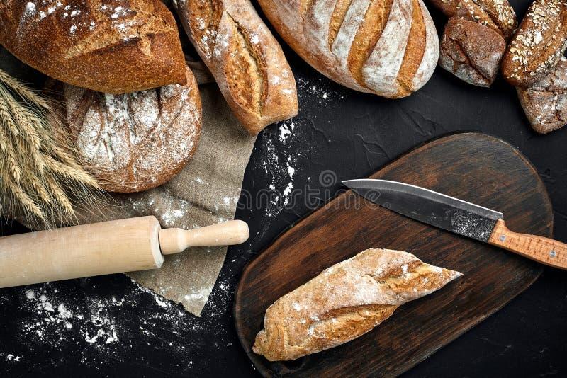 新鲜面包、木板和切刀在黑桌上 图库摄影