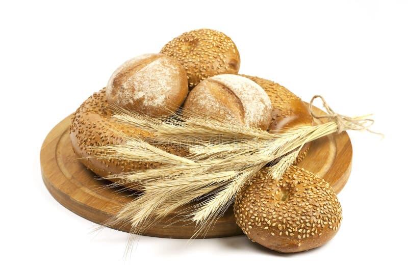 新鲜面包和麦子在木板 图库摄影
