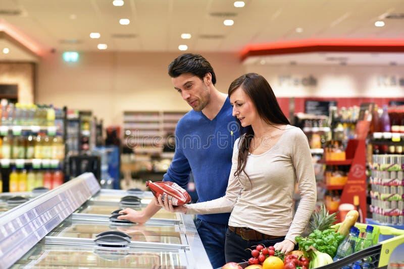 新鲜食品的年轻幸运的夫妇购物在超级市场- 库存照片