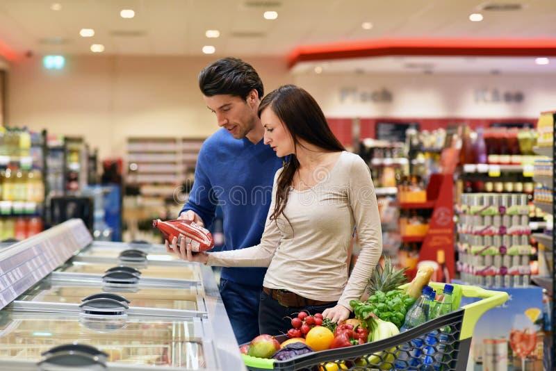 新鲜食品的年轻幸运的夫妇购物在超级市场- 库存图片