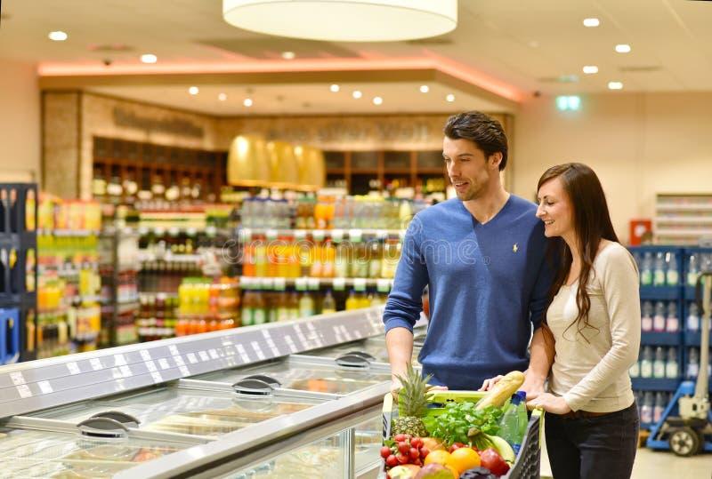 新鲜食品的年轻幸运的夫妇购物在超级市场- 免版税库存照片