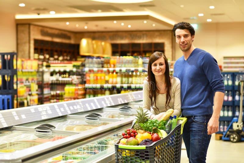 新鲜食品的年轻幸运的夫妇购物在超级市场- 免版税图库摄影