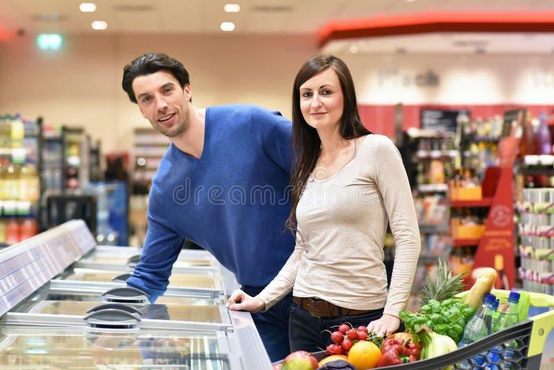 新鲜食品的年轻幸运的夫妇购物在超级市场- 图库摄影