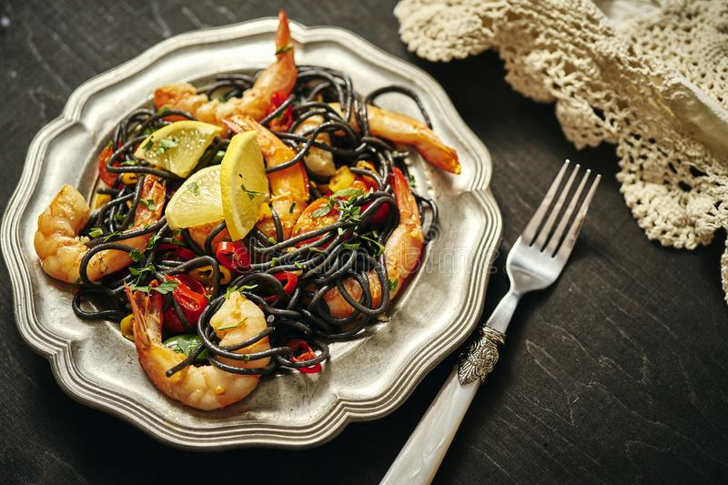 新鲜,可口黑意粉用烤大虾,蕃茄,在一个老银盘的辣椒 库存图片