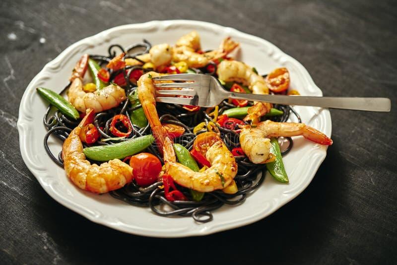 新鲜,可口黑意粉用烤虾,蕃茄,辣椒,在一块白色板材 免版税库存图片
