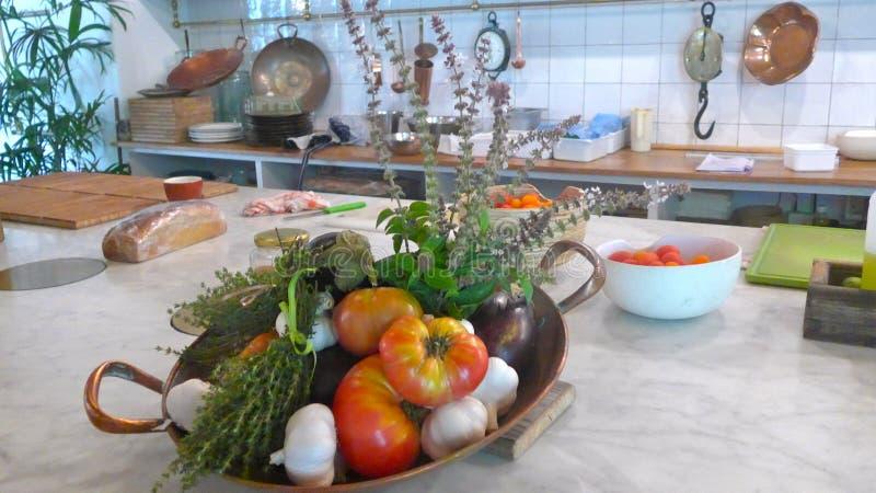 新鲜,有机菜,蕃茄、茄子、大蒜和草本,在一个碗在厨房用桌上 免版税库存照片