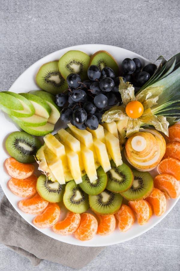 新鲜水果牌照 在一块白色板材的热带水果分类 顶视图 复制空间 图库摄影