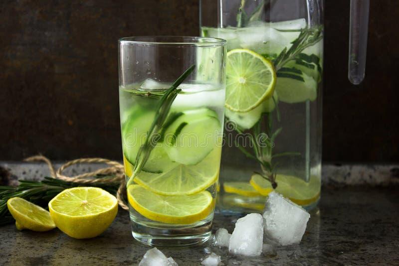 新鲜水果非酒精饮料鸡尾酒:黄瓜,石灰,迷迭香 一份健康饮料的概念 生锈背景的金属 库存图片