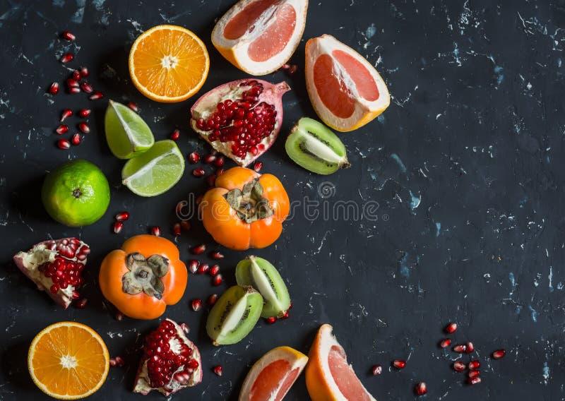 新鲜水果-葡萄柚,柿子,猕猴桃,石榴,桔子,石灰的变异 在黑暗的背景 库存图片