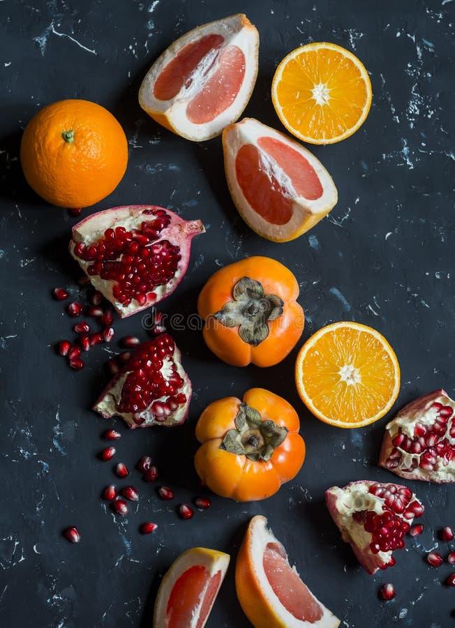 新鲜水果-葡萄柚,柿子,石榴的变异,橙色 在黑暗的背景 库存图片
