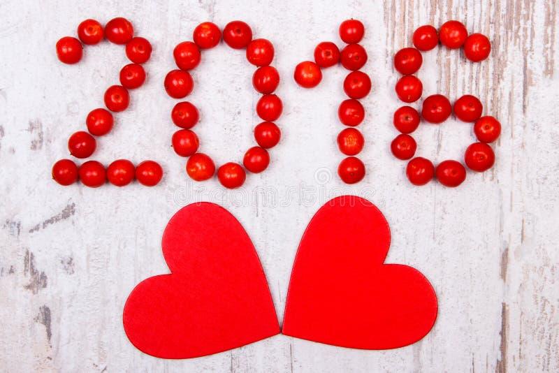 新年2016做了红色荚莲属的植物和红色木心脏在老木背景 免版税库存图片