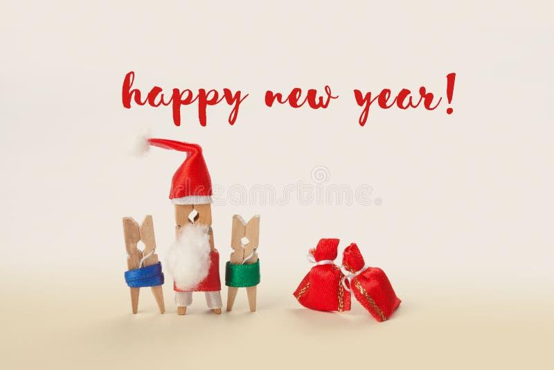 新年好与晒衣夹字符圣诞老人孩子和礼物的卡片概念 软的焦点, 库存照片