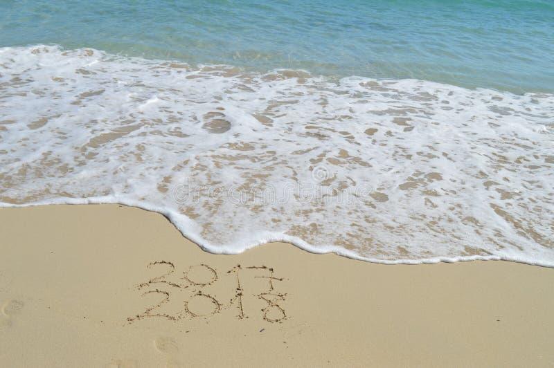 新年好2017年和2018手写在沙子 免版税库存照片