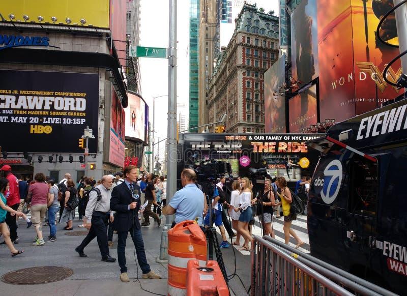 新闻工作者N J 从时代广场的Burkett报告,目击者新闻, NYC,美国 免版税库存照片