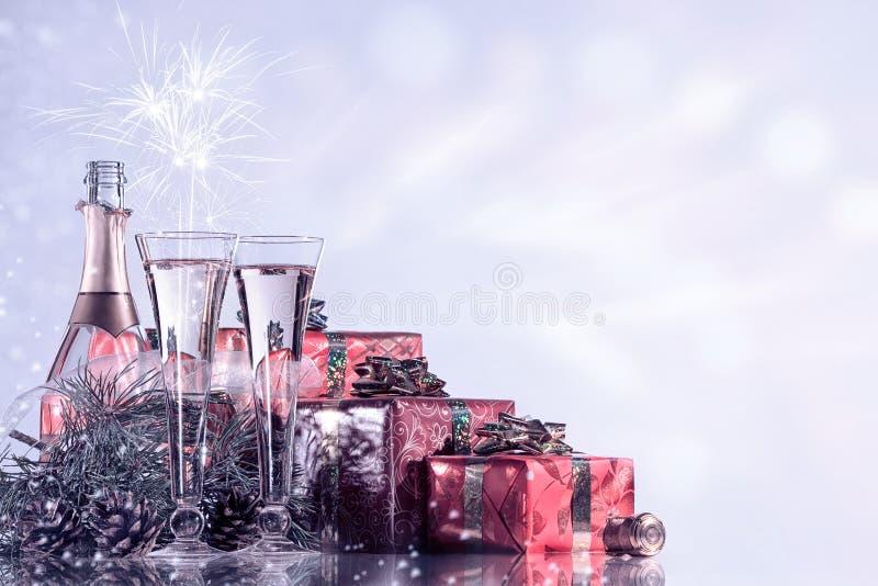 新年度和圣诞节庆祝 香宾、两个酒杯、烟花和礼物在眨眼睛假日背景 库存照片