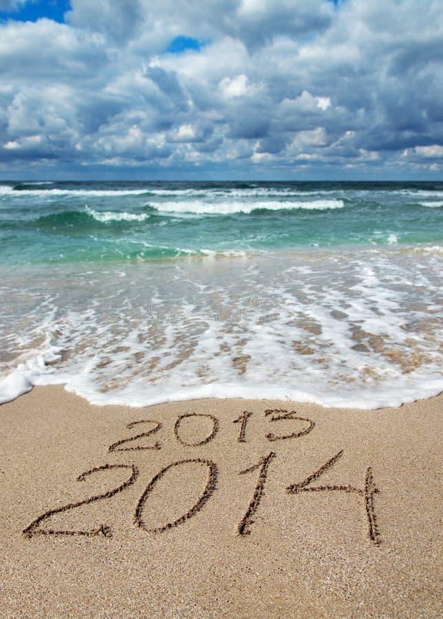 新年快乐2014冲走2013年在海海滩的概念 免版税库存图片