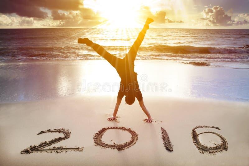 新年快乐2016年 在海滩的年轻人手倒立 库存图片