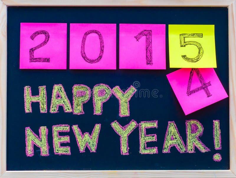 新年快乐2015年在黑板写的消息手,在便条纸陈述的数字,替换2014年的2015年 免版税图库摄影