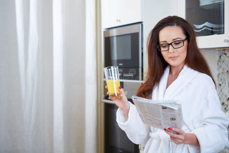 读新闻的妇女,当喝橙汁时 免版税库存照片