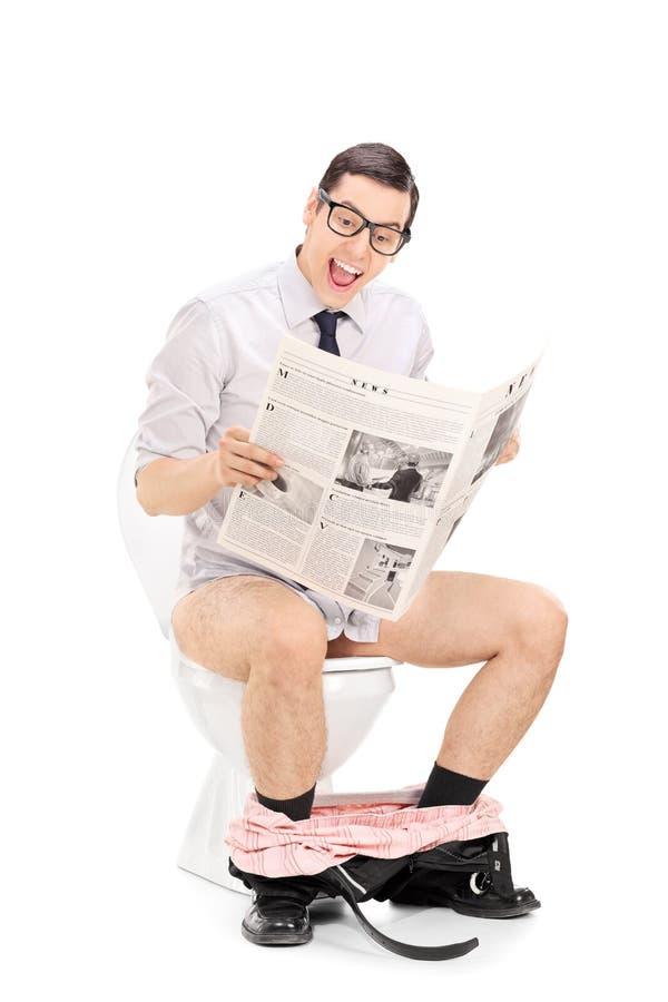 读新闻的快乐的人供以座位在洗手间 库存照片