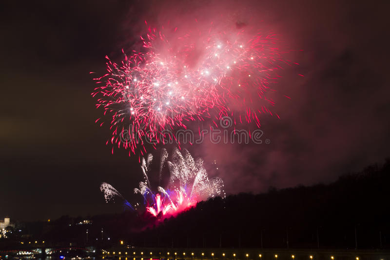 新年的惊人的明亮的红色和桃红色烟花庆祝2015年在有历史的城市的布拉格在背景中 库存照片