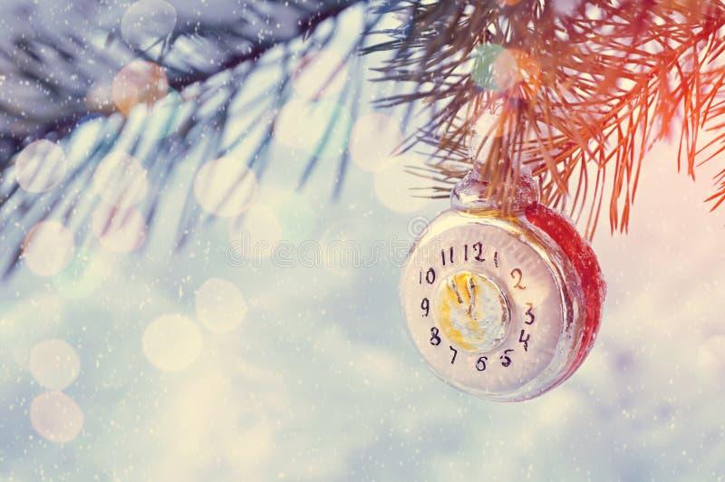新年背景新的年玻璃圣诞节玩具以显示在多雪的杉树分支的时钟的形式除夕, 库存照片