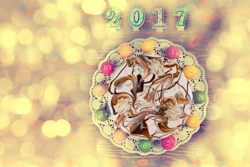 新年蛋糕和macarons作为一个时钟在蜡烛附近第2017 o 免版税图库摄影