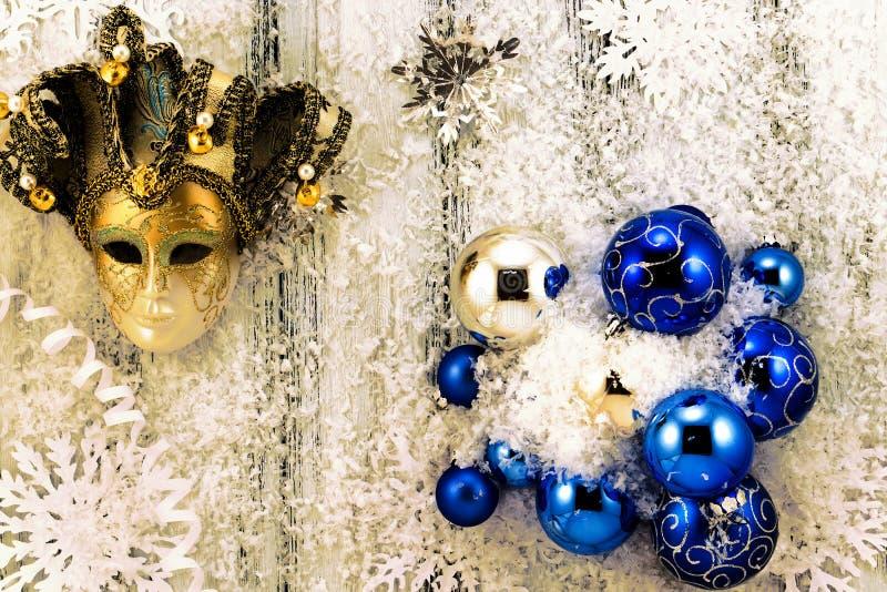 新年题材:圣诞树白色和银色装饰,蓝色球、雪,雪花,蜒蜒和金黄面具 免版税图库摄影