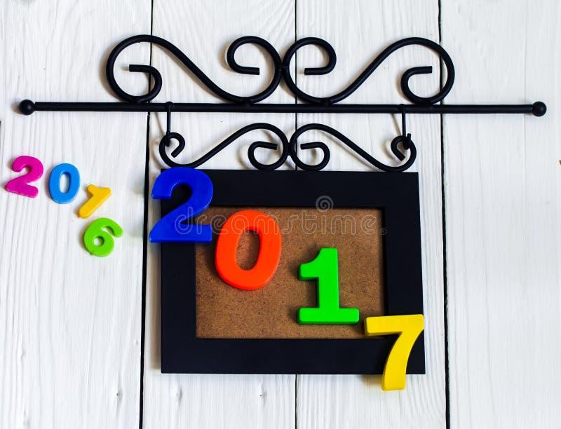 新年2017年,在画框的图在白色木背景 免版税图库摄影