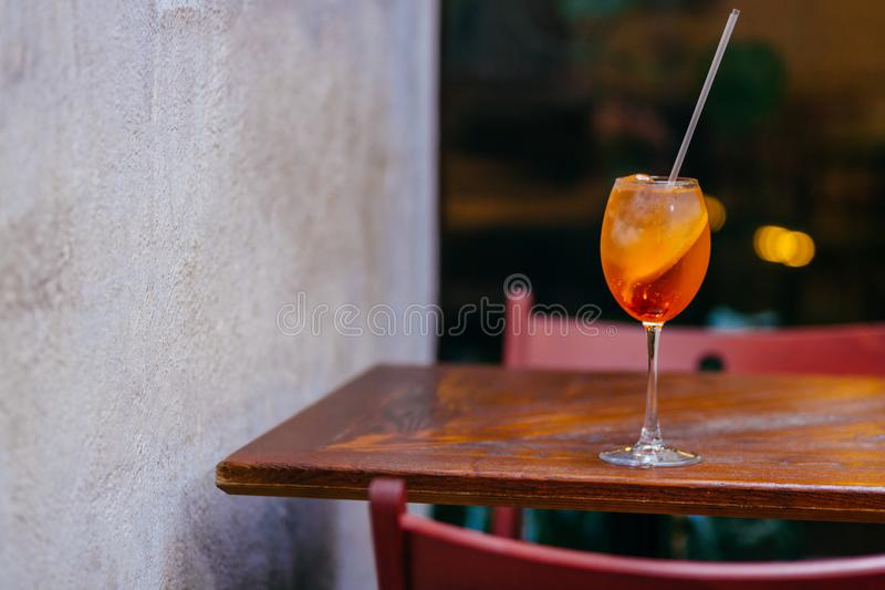 新Aperol精神coccktail,在木桌上在餐馆 夏天饮料水平的射击  与冰的橙色液体 Apereti 免版税图库摄影