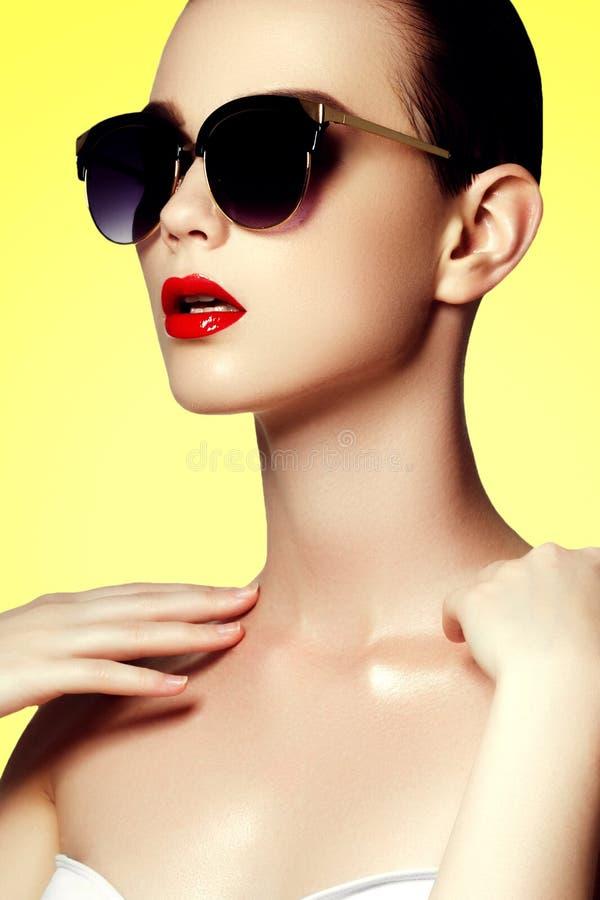 方式和秀丽 泳装的性感的妇女有金黄太阳镜的 免版税库存照片