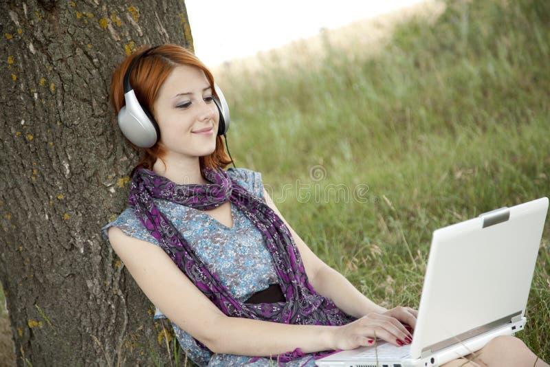 方式女孩耳机笔记本年轻人 免版税库存照片