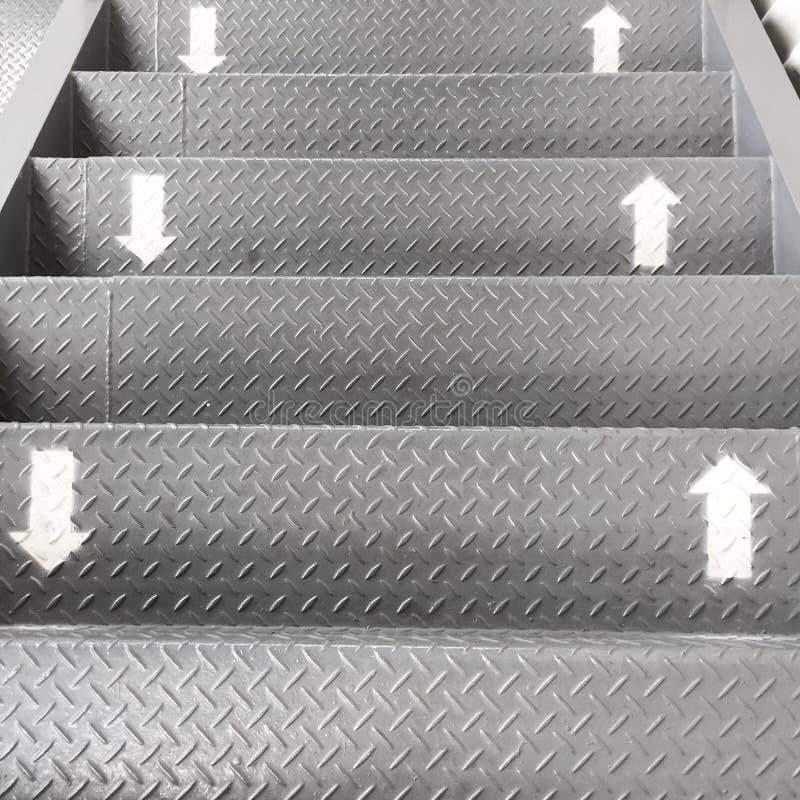 方式的标志上上下下在台阶 箭头在不锈钢梯子的白色被绘了 这是方向 库存照片