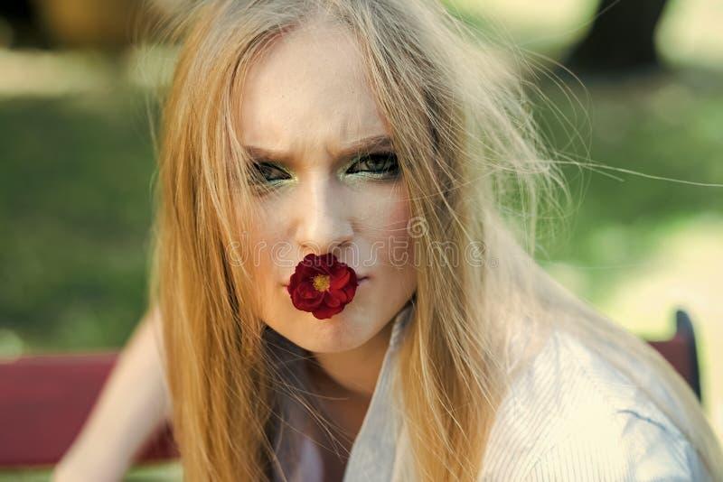 方式纵向 有金发的女孩和构成在春天拿着在嘴的红色花从开花的树室外 库存照片