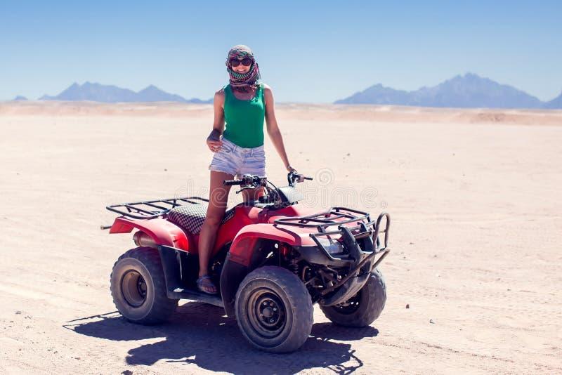 方形字体自行车的妇女在沙漠驾驶 免版税图库摄影