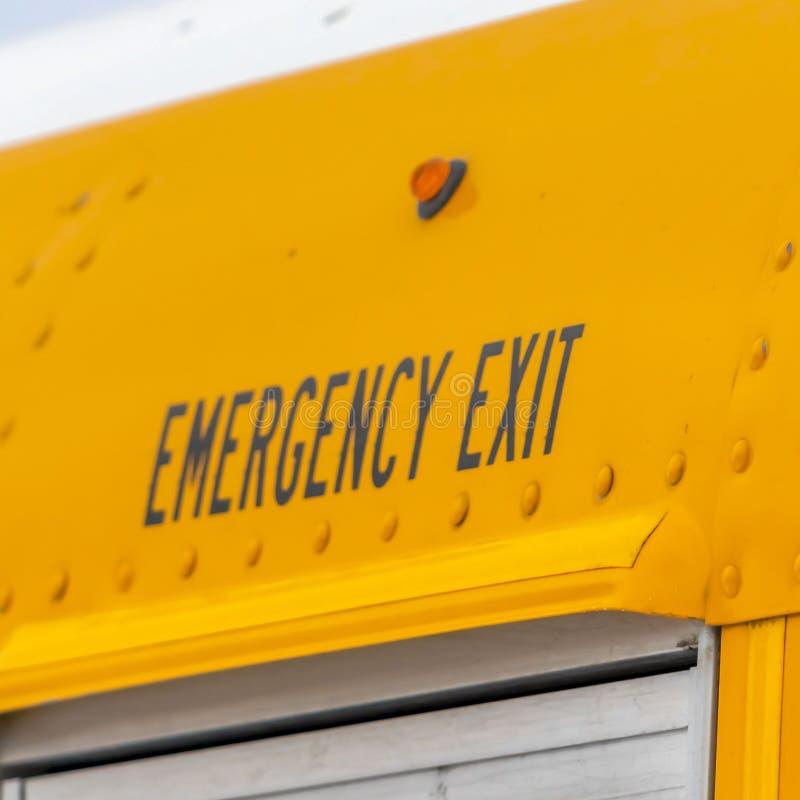 方形的关闭一黄色学校班车的外部有一个紧急出口标志的 库存照片